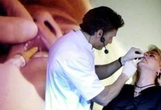 NLD-20030315-UTRECHT: Een model krijgt verdoving toegebracht voordat ze een cosmetische mondbehandeling ondergaat. De lippen worden ingespoten zodat ze voller worden. Dit weekend zijn in Utrecht op de vakbeurs Beaty en Trade voor schoonheidsspecialisten de nieuwste trends te zien op het gebied van gezichts-, lichaamsverzorging en make-up. ANP FOTO/JUAN VRIJDAG