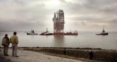 NLD-20050429-ANTWERPEN: Vanuit de Antwerpense haven is vrijdag een koeltoren van 65 meter hoog onderweg naar Vlissingen. Op de achtergrond is de kerncentrale van Doel te zien. De koeltoren, bestemd voor een gaswinningsveld in de Barentszee, wordt op een ponton en met behulp van vier slepers op de de Westerschelde versleept. ANP FOTO/LEX VAN LIESHOUT