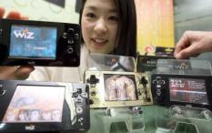 epa01695880 A model poses with the 'Wiz' portable gaming console, produced by Gamepark Holdings Co. of South Korea, as it hits store shelves on 13 April 2009. There are 13 games currently available for the unit, which features an organice light-emitting diode display.  EPA/YONHAP