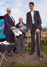 DEN HAAG - Sultan Kosen (R) en de langste man van Nederland, Rob Bruintjes (L) krijgen nieuwe schoenen aangeboden van Grote schoenenspecialist Georg Wessels (M). De langste man ter wereld, Sultan Kosen uit Turkije (2.46 meter), komt maandag op bezoek in Madurodam in Den Haag in het kader van de lancering van het boek Guiness World Records 2010. Hij krijgt het boek overhandigd van de langste man van Nederland, Rob Bruintjes (R, 2.21 meter). ANP ED OUDENAARDEN