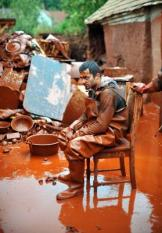 epa02377793 A local resident rests on a chair in the garden of his house covered with red mud while rescuing his belongings in Devecser, 164 kms southwest of Budapest, Hungary, 06 October 2010, after a dike of a reservoir containing red mud of an alumina factory in nearby Ajka broke two days ago, and over one million cubic meters of the poisonous chemical sludge inundated three villages, killing four persons and injuring over hundred. Three people are unaccounted for and hundreds of families have been evacuated.  EPA/TAMAS KOVACS **HUNGARY OUT**