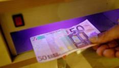NLD-20040503-PIJNACKER: Een winkelier controleert de echtheid van een Euro-biljet met behulp van een speciale lamp. ANPFOTO KOEN SUYK/MODEL RELEASED