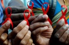 epa01950448 Indian activist display in their hands a 'Red ribbon' an international symbol of AIDS awareness that is worn by people to mark World AIDS Day, in Bangalore, southern India on 01 December 2009. On the first day of each December, people from all over the world turn their attention to HIV and AIDS for World AIDS Day dedicated to raising awareness of the AIDS pandemic caused by the spread of HIV infection.  EPA/JAGADEESH NV