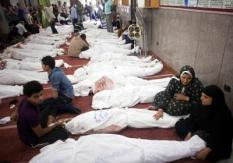 epa03825461 Egyptians sit next to the bodies of relatives and protesters who died following unrest the day before, at al-Imene mosque, Cairo, Egypt, 15 August 2013. At least 421 people were killed in Egypt on 14 August in violence linked to the police's break-up of two major protest camps in Cairo set up by supporters of deposed president Mohamed Morsi, the Health Ministry said. A total of 294 people were killed in Rabaa al-Adawiya in north-eastern Cairo and al-Nahda Square south of the capital during the crackdown on the campers. The rest of the deaths occurred in other areas of the country.  EPA/AHMED HAYMAN