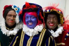 HILVERSUM - Het Nederlands Centrum voor Volkscultuur en Immaterieel Erfgoed (VIE) presenteert de Zwarte Piet anno 2014 (L) in het tv-programma Knevel & Van den Brink. Deze piet heeft geen kroeshaar, is bruin in plaats van zwart, heeft minder rode lippen en draagt geen oorringen. Tegenstanders van Zwarte Piet (R) presenteerden een paarse piet met rood haar (M). ANP KIPPA EVERT ELZINGA