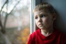 Een kleine jongen zit in het raam naar buiten te staren. Eenzaamheid komt ook onder jongeren voor.