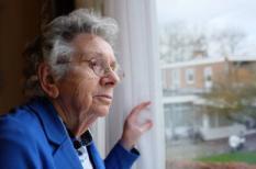Een alleenstaande bejaarde vrouw kijkt door haar raam naar buiten. Ouderen worden vaker getroffen door eenzaamheid.