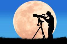 Een silhouet van een jongen die door een telescoop kijkt.