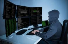 50691833 - rear view of hacker using computers to steal data in office