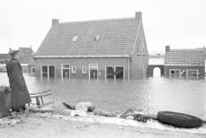 1953-02-13 00:00:00 OOSTDIJK - Watersnoodramp 1953. Politieman bij een ondergelopen huizen aan de Lavendeldijk. ANP PHOTO CO ZEYLEMAKER