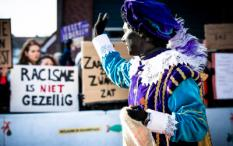 2018-11-17 13:44:26 ZAANSTAD - Demonstranten en een Zwarte Piet tijdens de landelijke intocht van Sinterklaas op de Zaanse Schans. De oer-Hollandse Zaanse Schans is dit jaar het decor van de landelijke intocht van de goedheiligman en zijn pieten. ANP FREEK VAN DEN BERGH
