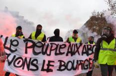 2018-12-01 09:58:30 Demonstrators hold a banner reading 'People in dire straits, let's kill the bourgeois' during a protest of Yellow Vests (Gilets jaunes) against rising oil prices and living costs on the Champs Elysees in Paris, on December 1, 2018.  Thousands of anti-government protesters are expected today on the Champs-Elysees in Paris, a week after a violent demonstration on the famed avenue was marked by burning barricades and rampant vandalism that French President compared to 'war scenes'.Alain JOCARD / AFP