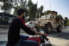 A Syrian man rides his motorcycle as a US military vehicle pulling out of a US forces base in the Northern Syrian town of Tal Tamr drives by, on October 20, 2019. US forces withdrew from a key base in northern Syria today, a monitor said, two days before the end of a US-brokered truce to stem a Turkish attack on Kurdish forces in the region.Delil SOULEIMAN / AFP