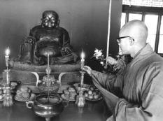 Boeddhistische monnik zet kaars bij Boeddha beeld.