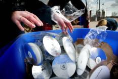 NLD-20020220-AMSTERDAM: Een grote partij CD's met illegale software wordt woendag in een contaier gegooid om later door de Amsterdamse Dienst Afvalverwerking vernietigd te worden in een 'schredder'. De illegale CD's zijn onlangs door de douane op Schiphol in beslag genomen. ANP FOTO/JUAN VRIJDAG