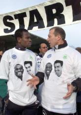 WOB02 - 20001112 - WOLFSBURG, GERMANY : Wolfsburg soccer player Charles Akonnor (L) from Ghana and Wolfsburg's coach Wolfgang Wolf display T-shirts with the pictures of Akonnor and his German teammate Zoltan Sebescen as they chat prior a marathon against xenophobia, Sunday 12 November 2000. EPA PHOTO DPA/RAINER JENSEN/rj/gr-hh