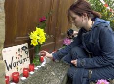 ERF31 - 20020426 - ERFURT, GERMANY : A girl lights a candle next to a sign reading Why ? at the entrance of the Gutenberg high school in Erfurt, 26 April 2002, following a shooting rampage here by a 19-year-old gunman who killed 17 people before shooting himself.