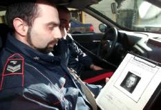 PAL01-20010221-PALERMO (ITALY)-An italian policeman holds a sheet with a picture of the escaped alleged mafia boss Bernardo Provenzano at Pontedera, in the region of Tuscany (north of Italy) Wednesday 21 February 2001. Last night Italian police arrested Vincenzo Virga, another alleged mafia boss in Trapani (Sicily, south of Italy) . EPA PHOTO ANSA PHOTO /FRANCO SILVI