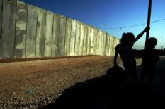 Palestinian Children plays near the new seperation wall t built near the west bank vilage of Mafha, Wednesday 22 October 2003 . Israel vowed to press on with the construction of its vast barrier in the West Bank despite a UN resolution condemning the project and demanding it to be halted. EPA/PAVEL WOLBERG