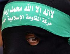 A Palestinian masked militant from Hamas takes part in the funeral of Momen El-Mghari, aged 21, at the al Maghazi refugee camp, central Gaza Strip, early Friday 07 November 2003. El-Mghari a militant from Hamas was killed during clashes with Israeli troops, who entered the camp after soldiers were fired upon. EPA/MOHAMMED SABER