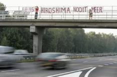 NLD-20040806-EINDHOVEN: De bekende activiste Mariette Moors (R) hangt vrijdag een spandoek op boven de A2 bij Eindhoven. Het is precies 59 jaar geleden dat de Amerikanen een atoombom gooiden op de Japanse stad Hiroshima. ANP FOTO/JASPER JUINEN