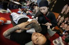 NLD-20050603-AMSTERDAM: Een man laat zich vrijdag tatoeeren middels de Irezumi-techniek. Hierbij wordt  geen gebruik gemaakt van de traditionele naalden maar van een scherpe bamboestok. Internationaal bekende  tattoo-artiesten en liefhebbers van deze kunstvorm zijn dit weekeinde bijeen op de Internationale  Tattooconventie in de Amsterdamse RAI. ANP FOTO/MARCEL ANTONISSE