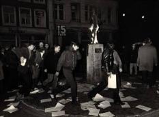 Protest bij het 'Lieverdje'. De provo's hielden regelmatig happenings rond het beeld van het Amsterdamse Lieverdje op het Spui. Dit protest richtte zich tegen het politie-optreden op 19 maart 1966 nadat bij de opening van een fototentoonstelling rellen waren uitgebroken. De fototentoonstelling ging juist over het politieoptreden van 10 maart (huwelijk prinses Beatrix)./Provo's, Happening rond 'Lievertje'20.03.1966