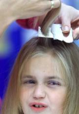 DEN HAAG/20001011 - De haren van dit meisje worden woensdag gecontroleerd op haarluizen en neten. De GGD Den Haag heeft woensdag 11 oktober uitgeroepen tot Nationale Luizendag. In het Atrium van het stadhuis in Den Haag kon men zich laten kammen en informeren over luizen en neten. ANP Foto - TOUSSAINT KLUITERS