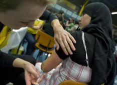 HELMOND - Een meisje wordt maandag in een sporthal in Helmond ingeent tegen baarmoederhalskanker. De GGD heeft ruim 380.000 meisjes tussen de dertien en zestien jaar in de regio Noord-Brabant opgeroepen zich te laten vaccineren tegen baarmoederhalskanker. Jaarlijks krijgen zeshonderd vrouwen deze ernstige ziekte. ANP PHOTO ED OUDENAARDEN