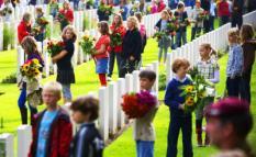 OOSTERBEEK - Schoolkinderen staan met bloemen bij de graven van de slachtoffers die omkwamen bij de de Slag om Arnhem,  zondag op de Airborne Begraafplaats in Oosterbeek. Bij de Slag om Arnhem zijn circa 11.000 geallieerde militairen ingezet, ruim 1800 van hen zijn bij de oorlogshandelingen om de brug over de Rijn bij Arnhem te veroveren om het leven gekomen. De 64e herdenking van de Slag om Arnehm en oparatei Market Garden trok honderden belangstellenden. ANP PHOTO ROBIN UTRECHT .